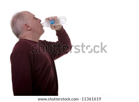 An older man in a long sleeved shirt drinking bottled water against a white background