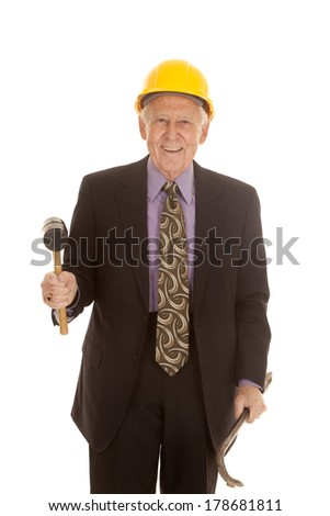 an older man in his hard hat holding on to his construction tools. - stock photo