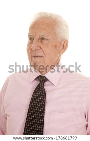 An older man in his pink shirt looking to the side. - stock photo