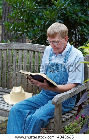 An older man in overalls sitting outside reading the Bible.
