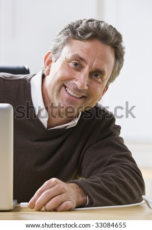 An older man is sitting at a desk and smiling at the camera.  Vertically framed shot.