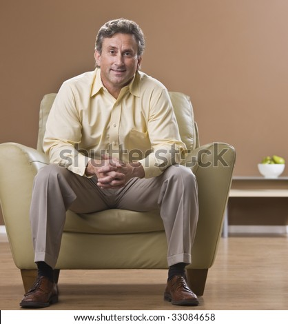 An older man is sitting in a chair in his living room and smiling at the camera.  Square framed shot.