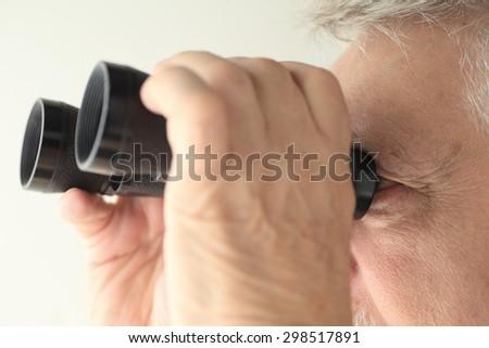 An older man looking through an old pair of binoculars - stock photo