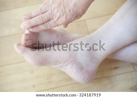 An older man reaches to touch his toes from a sitting position. - stock photo