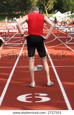 An older man ready to run a race - stock photo
