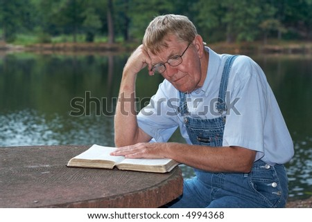 An older man sitting by the lake reading the Bible.