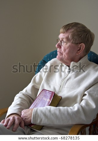 An older man sitting in a chair with his Bible.
