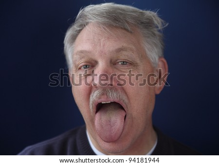 an older man sticks out his tongue as if for a medical exam - stock photo