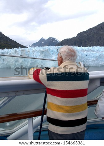 An older man views the Ried Glacier in Glacier Bay, Alaska from the deck of a cruise ship. - stock photo