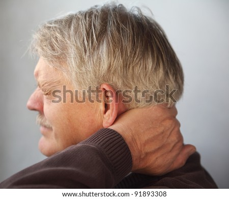 an older man wincing from pain in the back of his neck - stock photo