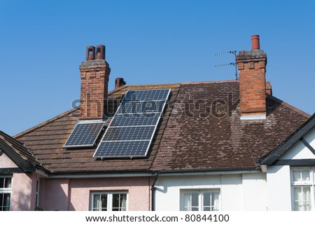 An older (1930s) house has solar panels installed on the roof. Copyspace available in sky. - stock photo