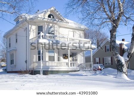 An older style family home after a snowfall. - stock photo