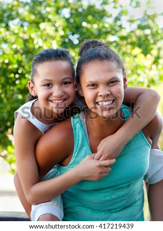 An older teenage girl carries a younger girl on her back, both smiling. - stock photo