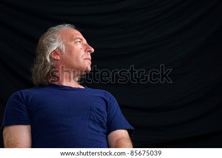 An older white male is looking towards copy space in blue t shirt against black background taken from low angle. - stock photo