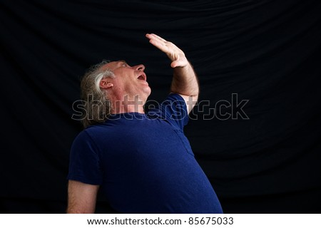 An older white man is cowering in fear and has hand up in front of face to protect him. - stock photo
