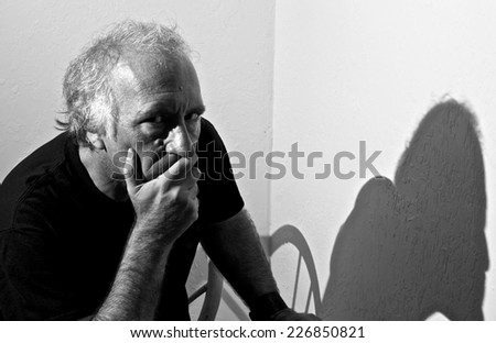 An older white man is looking directly at viewer with a serious look in his eyes and covering his mouth with his hand. - stock photo