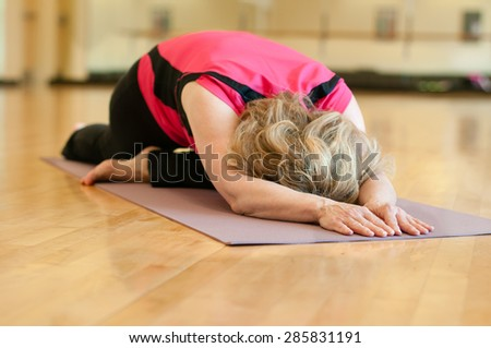 An older woman doing yoga practices pigeon pose. The blond woman is wearing a bright pink shirt and she is practicing on a mauve colored yoga mat. She is alone in a studio classroom.