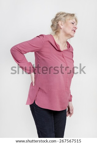 an older woman has pain and holds the back - stock photo