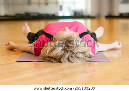 An older woman in a pink yoga outfit rests on the floor of the gym room in savasana (corpse) pose after yoga class, - stock photo