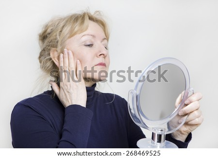 an older woman looking in a hand mirror on her face - stock photo
