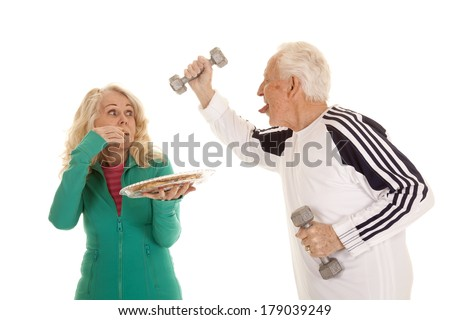 An older women tempting her husband who is working out with weights, with a plate full of cookies. - stock photo