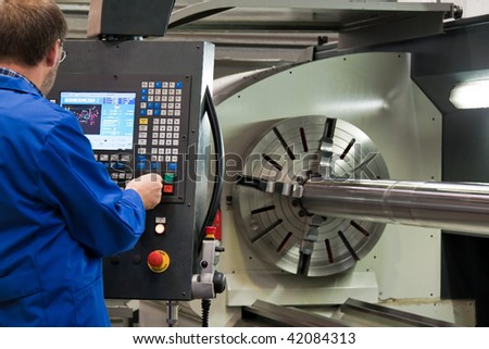 An older workers in the metal industry with CNC milling machine. - stock photo