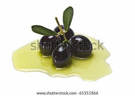 An olive branch with four premium olives and leaves on some olive oil and isolated on a white background. - stock photo