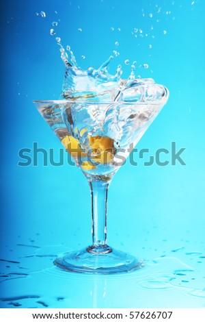an olive splashing into a martini - stock photo