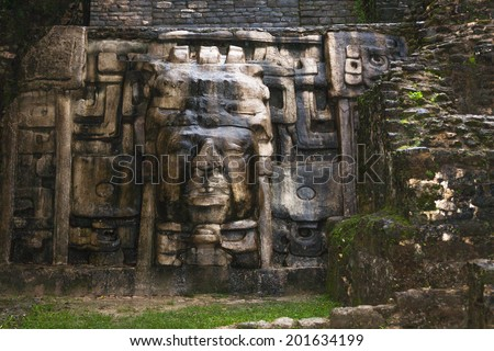 An Olmec style face adorns the side of the Mask Temple at the Mayan site of Lamanai in Belize. - stock photo