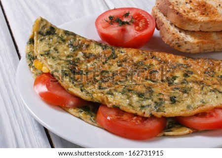 An omelet with spinach and tomatoes. Healthy and tasty breakfast - stock photo