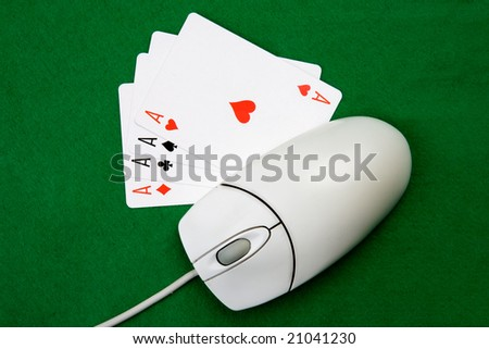 An online gaming concept with computer mouse, four aces and green felt - stock photo