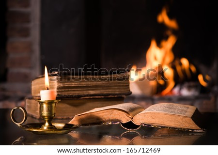 An open Bible with a burning candle in front of fireplace - stock photo