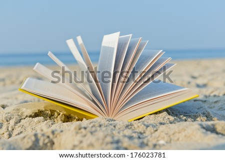 An open book laying on a sandy beach. - stock photo