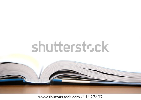 An open book on a desk in a class room - stock photo