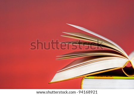 An open book on a pile of  other books books - stock photo