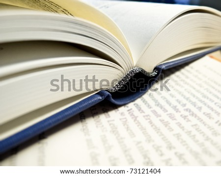 An open book on a sheet of paper - stock photo