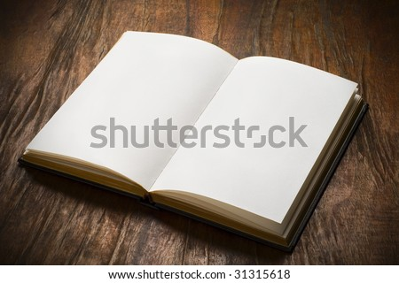 an open book with blank pages on wood table - stock photo
