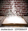 An open book with letters falling into the pages - stock photo
