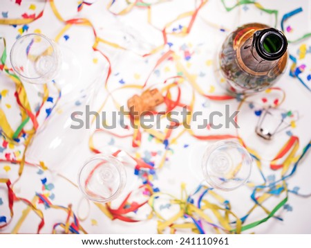 an open bottle of champagne with confetti - stock photo