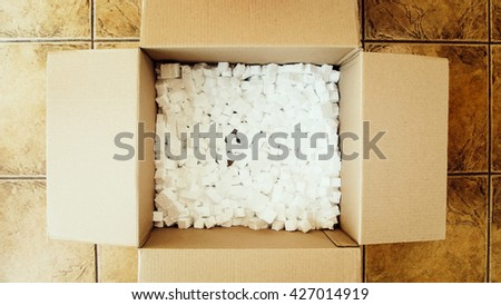 An open box with filling material inside, top view. Present box, big shipping box. Opening a parcel, unpacking box, surprise. Delivery, shipping service, opening cardboard box or parcel. - stock photo