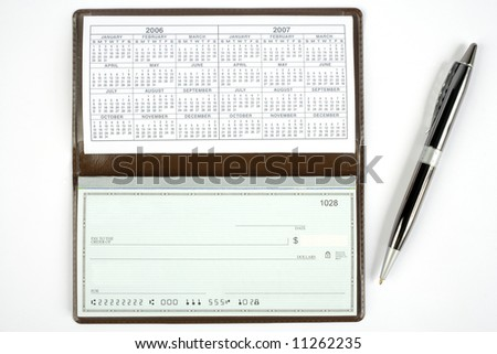An open checkbook showing the calendar with a pen to the right side. - stock photo