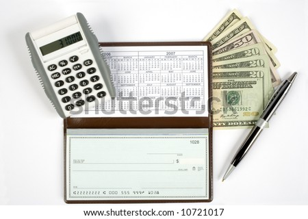 An open checkbook showing the calendar with a pen to the right side. Has a calculator and cash with it. - stock photo