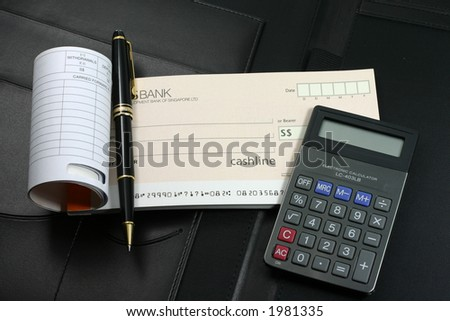 An open cheque book, calculator, and a black-gold roller ball pen lying on top of a black executive leather folder. - stock photo