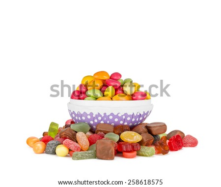 An open Easter egg filled with colorful easter egg candy on a pile of other colorful candy. Easter concept. - stock photo