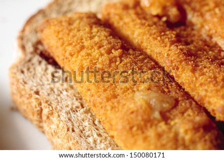 An open fish finger sandwich on a slice of wholemeal bread - stock photo