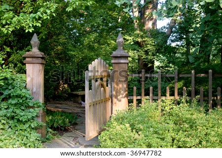 An open garden gate offers an invitation to enter into a shady and secluded area. - stock photo