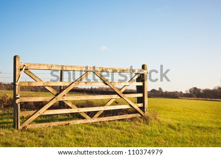 An open gate on farmland in England - stock photo