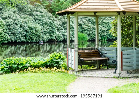 An open gazebo near a pond or lake in public park. - stock photo