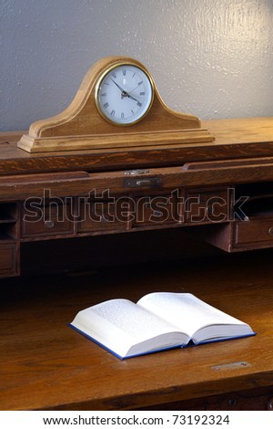 an open hardcover book literature sits on antique wood roll top desk with mantel clock in - Mantel Clock