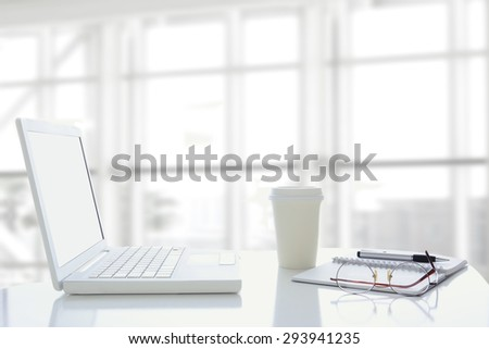 An open laptop computer in modern office window. The window is out of focus and high key. Desk also had disposable coffee cup, a note pad and eye glasses. - stock photo